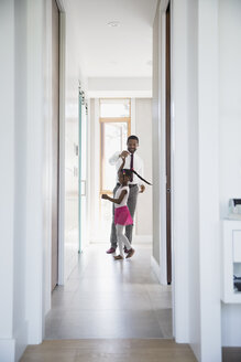 Father spinning daughter dancing in hallway - HEROF05336