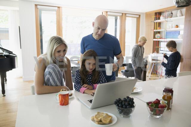 Family in pajamas using digital tablet in morning kitchen - HEROF05348