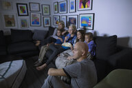 Family eating popcorn watching movie in dark living room - HEROF05354