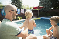 Father applying sunscreen to back of son at sunny poolside - HEROF05369