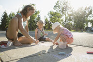 Family drawing with sidewalk chalk on sunny sidewalk - HEROF05375