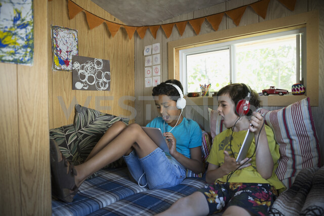 Enthusiastic boys with headphones using digital tablets in treehouse - HEROF05378