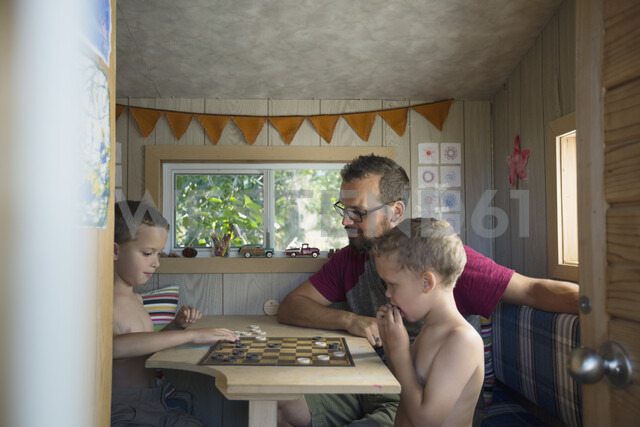 Father and sons playing checkers at table in treehouse - HEROF05387