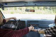 Couple holding hands driving in camper van - HEROF05390