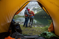 Couple hugging and looking at lake view outside of camping tent - HEROF05396