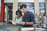 Couple browsing book at bookstore storefront sidewalk bin - HEROF05411