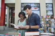 Couple browsing book at bookstore storefront sidewalk bin - HEROF05411