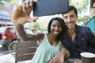 Couple taking selfie with camera phone at sidewalk cafe - HEROF05414