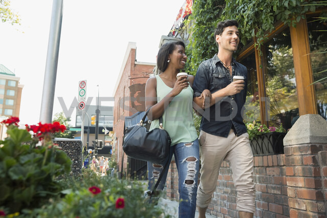 Couple walking with coffee on urban sidewalk - HEROF05417 - Hero Images/Westend61
