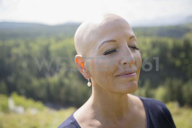 Close up serene female cancer survivor with shaved head and eyes closed - HEROF05432