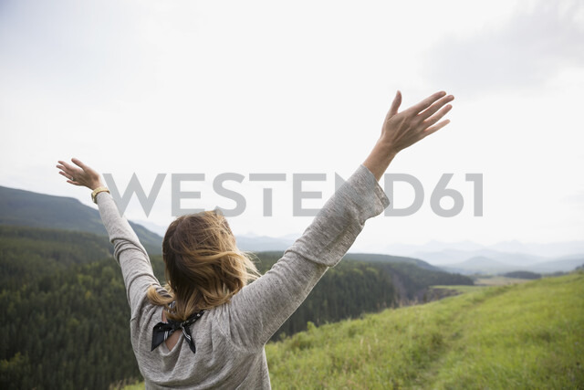 Exuberant woman with arms outstretched in remote rural field - HEROF05435