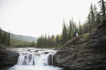 Couple on rocks above remote waterfall - HEROF05438