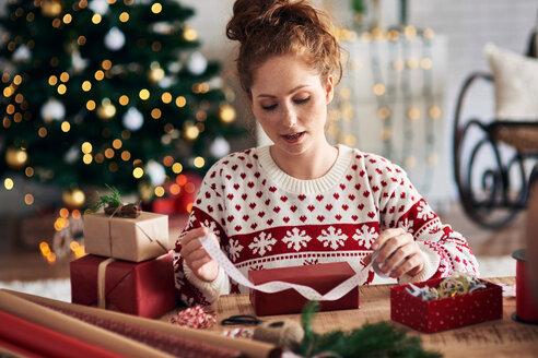 Woman tying ribbon on Christmas present - CUF48168