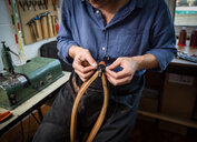 Leatherworker stitching leather in workshop, mid section - CUF48210