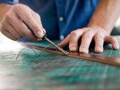 Leatherworker trimming leather for handbag strap in workshop, close up of hands - CUF48213