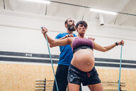 Trainer guiding pregnant woman using ropes in gym - CUF48216
