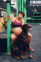 Pregnant woman and pet dog sitting in gym - CUF48219