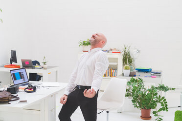 Crazy businessman playing air guitar in office - CUF48228
