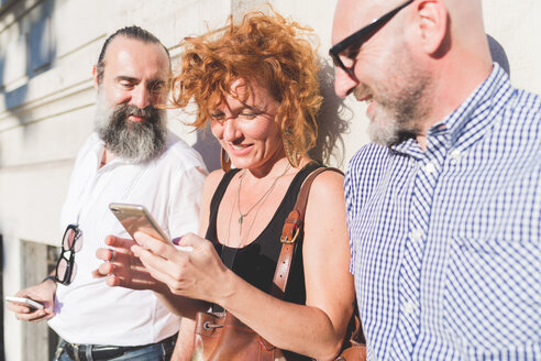 Mid adult woman and male friends leaning against wall looking at smartphone - CUF48237