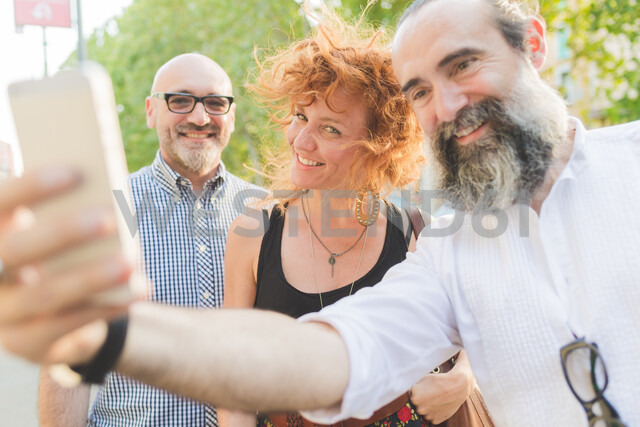 Mid adult woman and male friends taking smartphone selfie on city street - CUF48240 - Eugenio Marongiu/Westend61