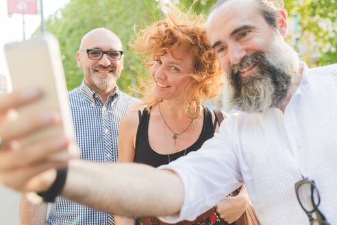 Mid adult woman and male friends taking smartphone selfie on city street - CUF48240