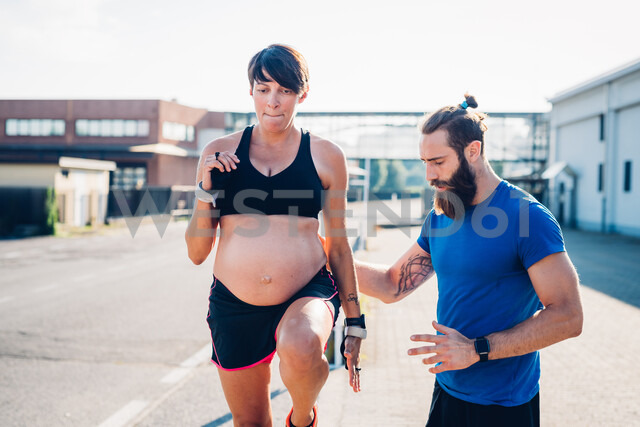 Pregnant woman and personal trainer working out outdoors - CUF48255