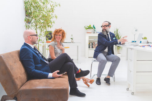 Businessmen and woman having discussion at meeting on office sofa - CUF48258