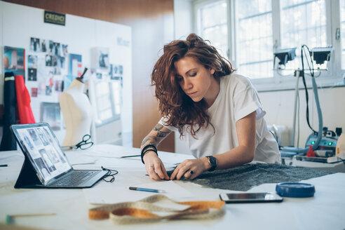 Fashion designer pinning fabric cutouts - CUF48267