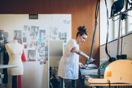 Fashion designer ironing in her work studio - CUF48270