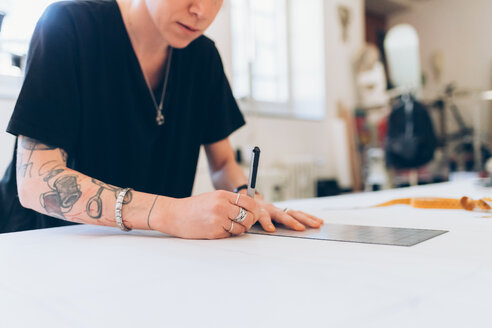 Fashion designer drawing and creating dressmaker's pattern - CUF48279