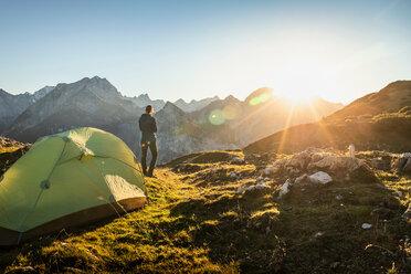 Hiker by tent enjoying view, Karwendel region, Hinterriss, Tirol, Austria - CUF48303
