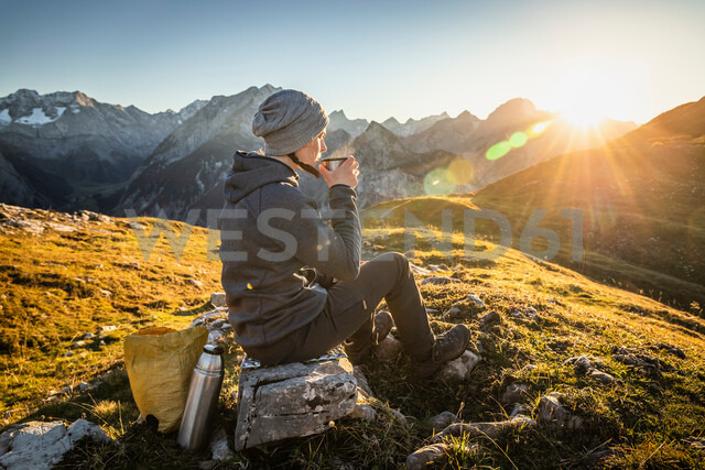 Hiker taking break with warm drink, Karwendel region, Hinterriss, Tirol, Austria - CUF48306