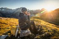 Hiker taking break with warm drink, Karwendel region, Hinterriss, Tirol, Austria - CUF48306