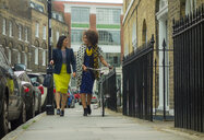 Women talking and walking bicycle on kerb, London, UK - CUF48324