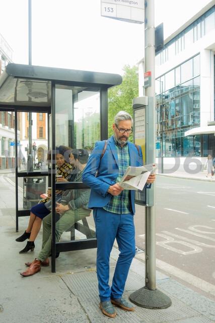 Man waiting at bus stop, London, UK - CUF48327