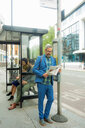 Man waiting at bus stop, London, UK - CUF48327