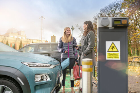 Female shoppers charging electric car at charge point, Manchester, UK - CUF48330