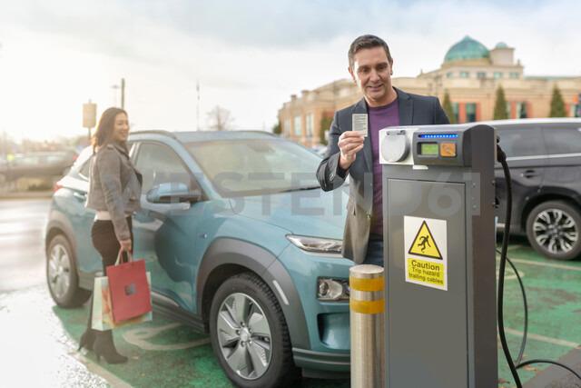 Man and woman charging electric car at car charging park, Manchester, UK - CUF48333