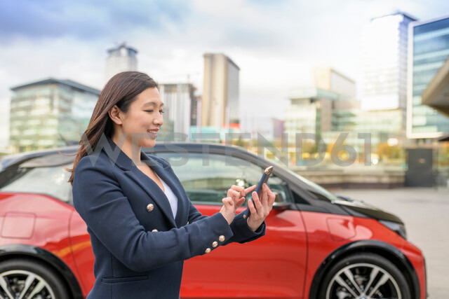 Woman checking electric car charge on mobile phone app, Manchester, UK - CUF48339