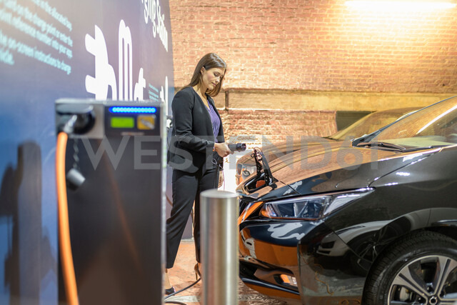 Businesswoman plugging in car at electric vehicle charging station, Manchester, UK - CUF48345 - Monty Rakusen/Westend61