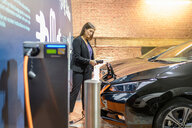Businesswoman plugging in car at electric vehicle charging station, Manchester, UK - CUF48345