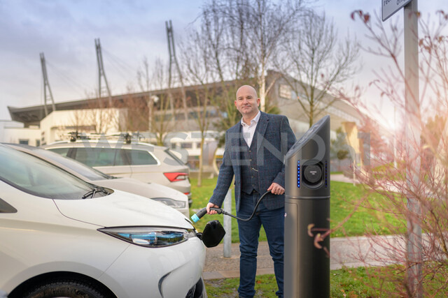 Portrait of businessman plugging in electric car at charging point, Manchester, UK - CUF48348