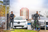 Man and woman with mountain bike at electric car charging point, Manchester, UK - CUF48351