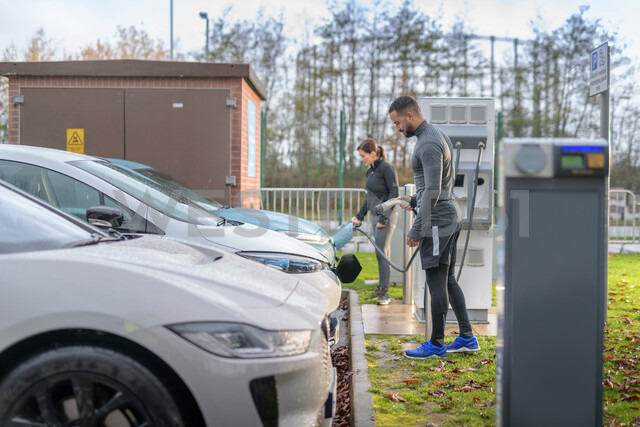Sportsman and woman charging electric car at charging bay, Manchester, UK - CUF48354 - Monty Rakusen/Westend61