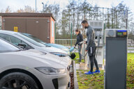 Sportsman and woman charging electric car at charging bay, Manchester, UK - CUF48354