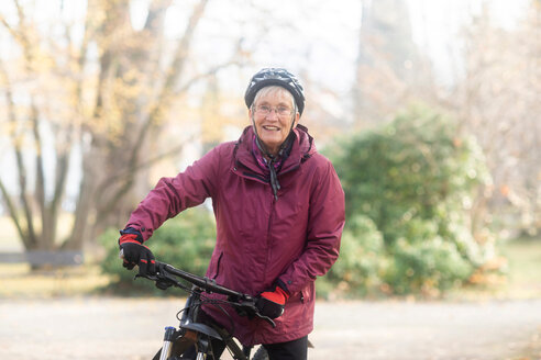 Senior woman on bicycle in park - CUF48360