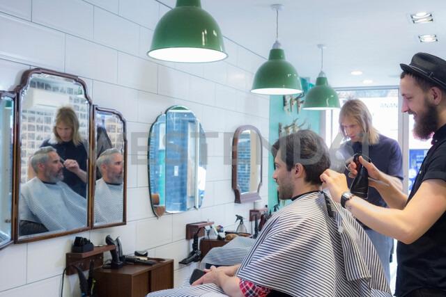 Barbers working in barbershop - CUF48363