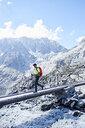 Hiker crossing narrow bridge, Mont Cervin, Matterhorn, Valais, Switzerland - CUF48396