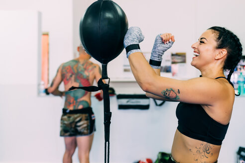 Woman using punch bag in gym - CUF48399