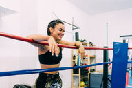 Laughing female boxer leaning over boxing ring ropes - CUF48402